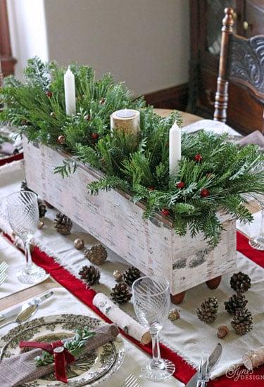 centro de mesa de madera con velas y ramas dentro