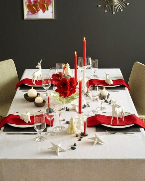 decoración sencilla de una mesa con velas rojas, copas y ciervos en los platos