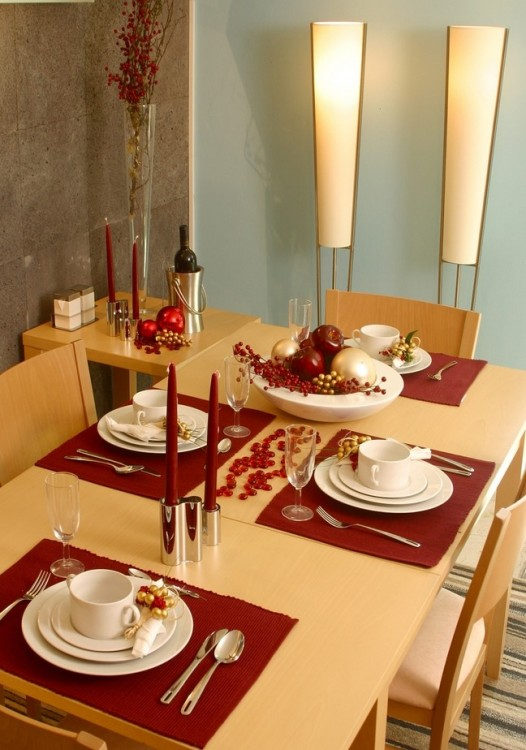 decoración de una mesa con pequeños manteles y velas en color rojo