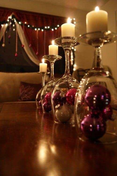 copas de vino al revés con esferas adentro y unas pequeñas velas encendidas en la parte superior