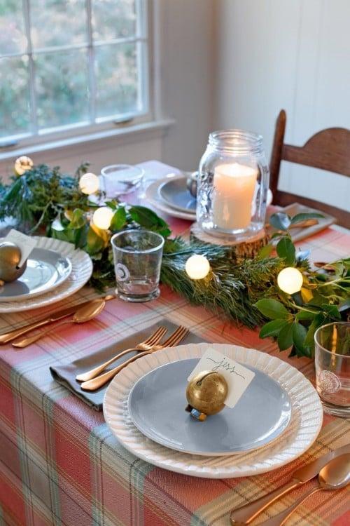 ramas con frascos y velas en el centro de mesa