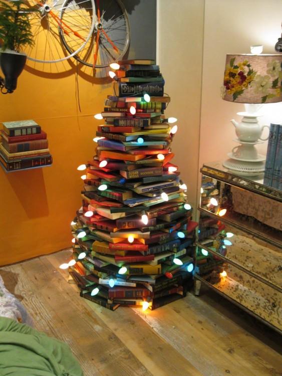 libros apilados formando un árbol de navidad con luces