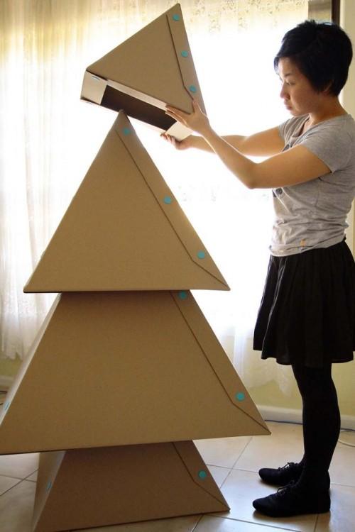 mujer apilando cajas de cartón como árbol de navidad
