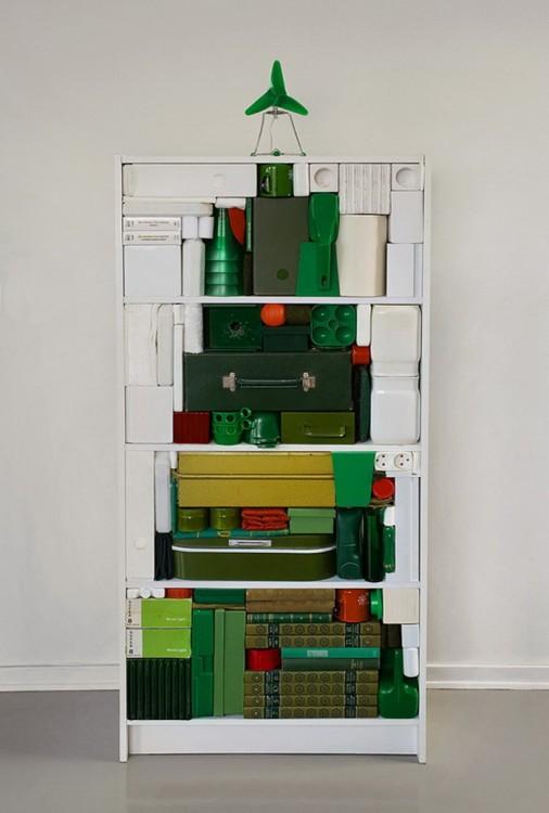 Librero con cosas de colores apiladas en forma de árbol de navidad