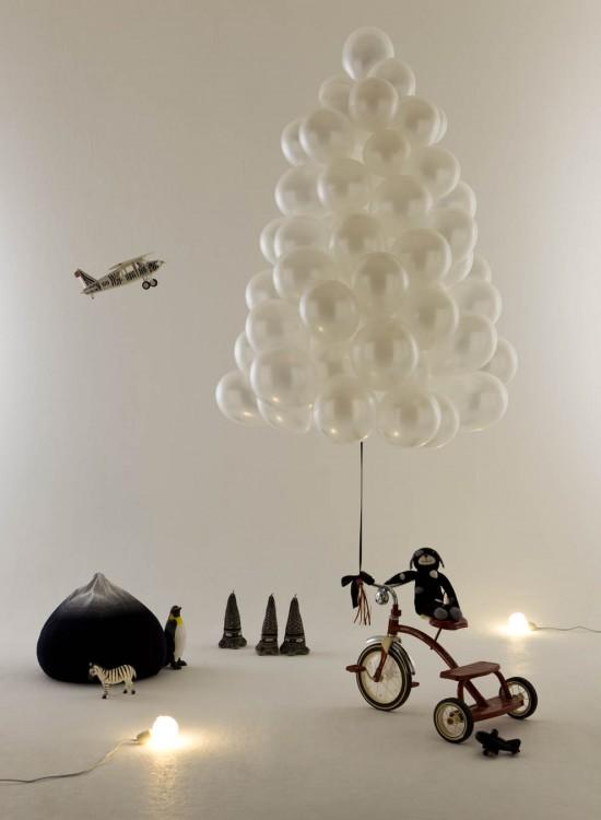 árbol de globos blancos amarrado a un triciclo en una casa
