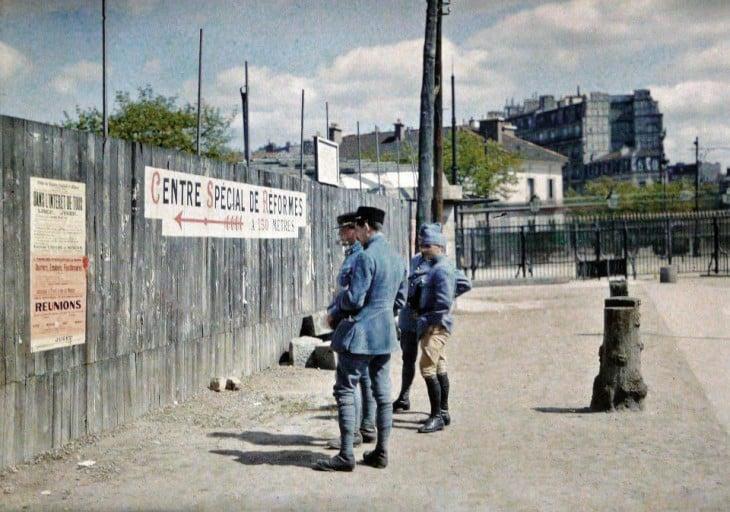 Soldados de París leyendo un anuncio en la pared