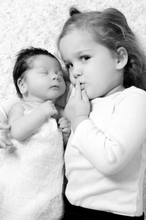 Fotografía de una niña acostada con su hermano bebé