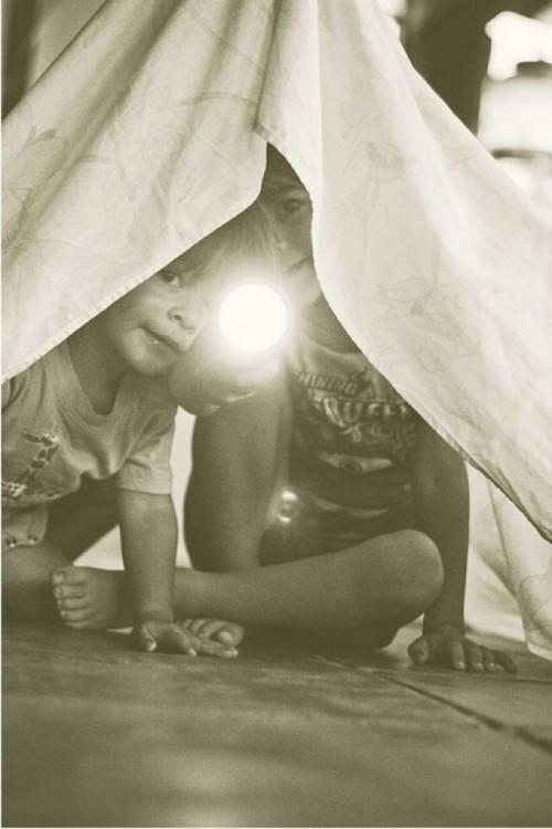 Dos niños debajo de una sabana con una linterna en la mano