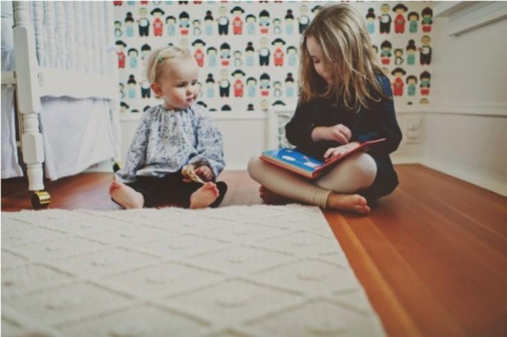 dos niñas sentadas en el suelo viendo un libro