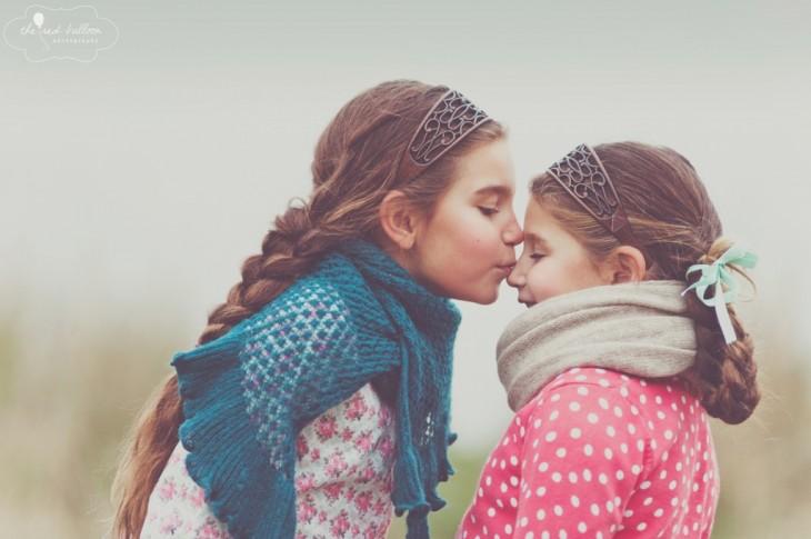 foto de una niña dando un beso en la nariz de su hermana