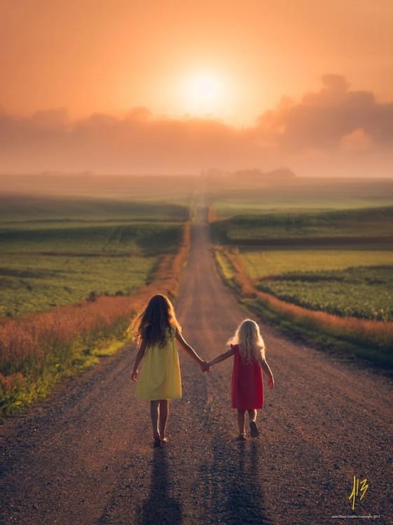 Dos niñas caminando por un camino agarradas de la mano