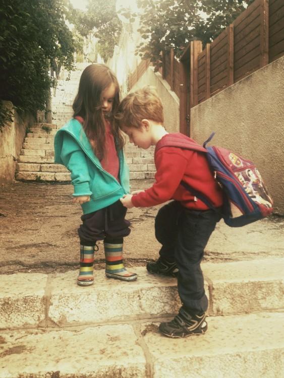 niño abrochando la chamarra de su hermanita