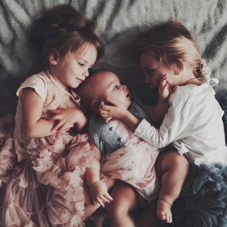 tres niñas acostadas sobre una cama