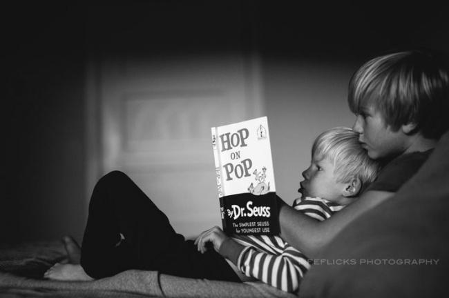 dos niños acostados en una cama leyendo el libro hop on pop