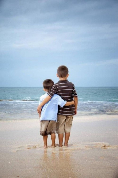 dos niños abrazados frente a la playa