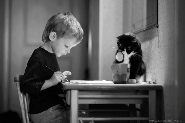 niño pintando en una mesa junto a su gato