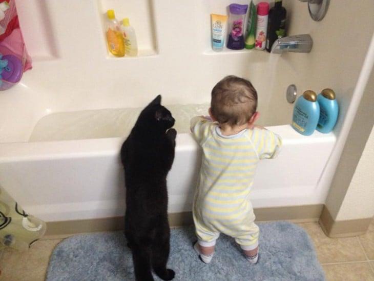 bebé parado junto a su gato frente a la bañera