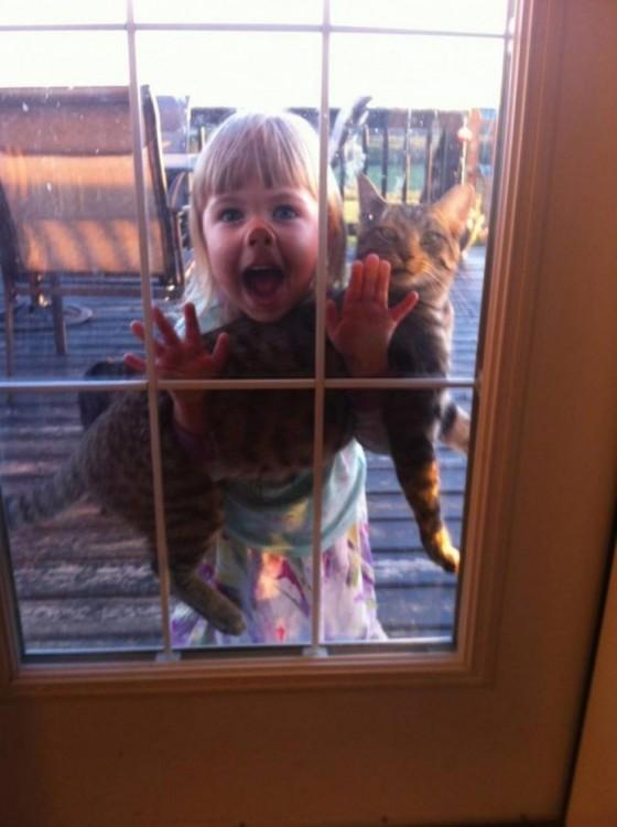 niña asomándose por una puerta con un gato en sus brazos