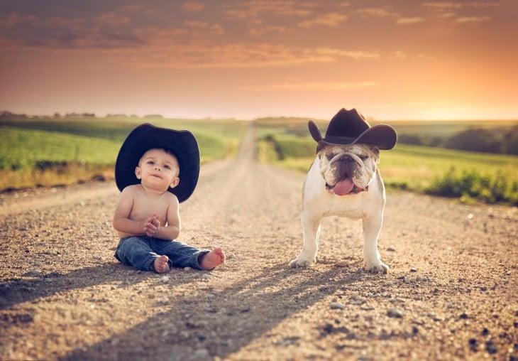 bebé con un sombrero sentado a un lado de su bulldog con sombrero