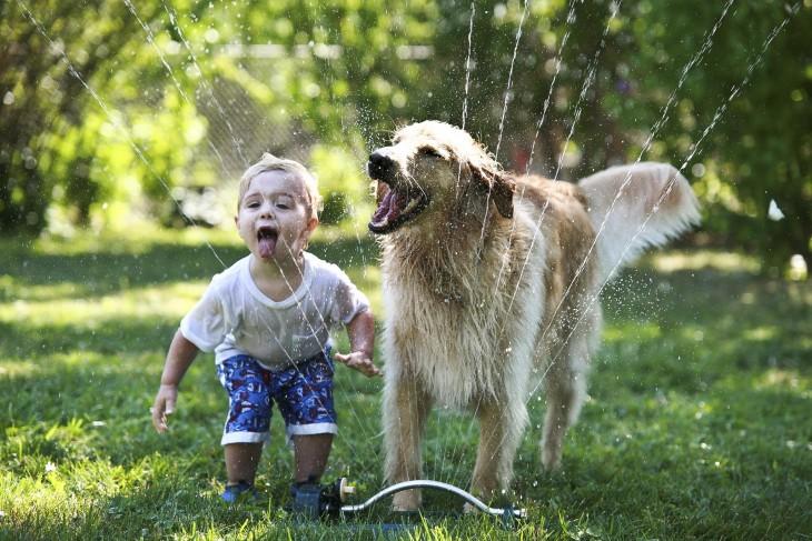 niño tomando agua en un jardín junto a su perro