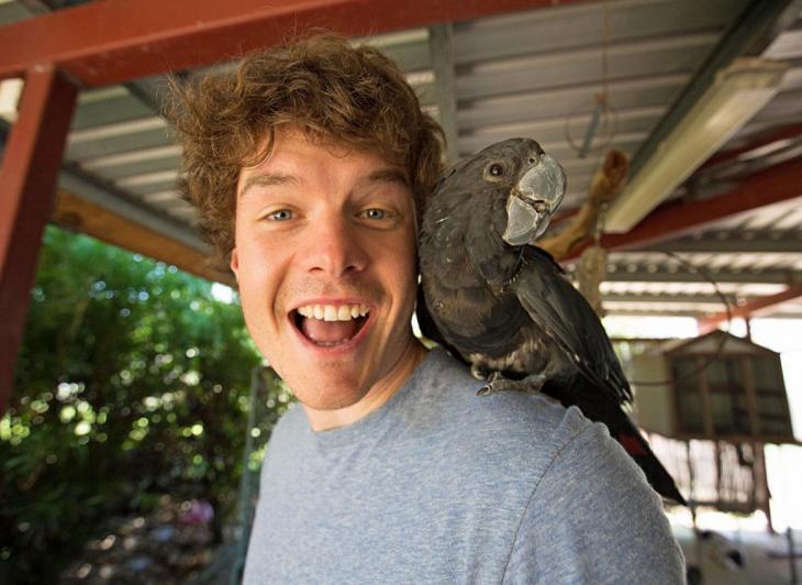 selfie de un chico con un ave parada en su hombro