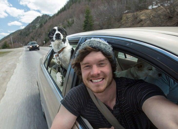 Selfie de un chico dentro de un carro con un perro en la parte trasera