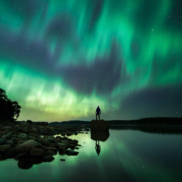Hombre parado sobre una roca cerca de un lago en una noche en Finlandia