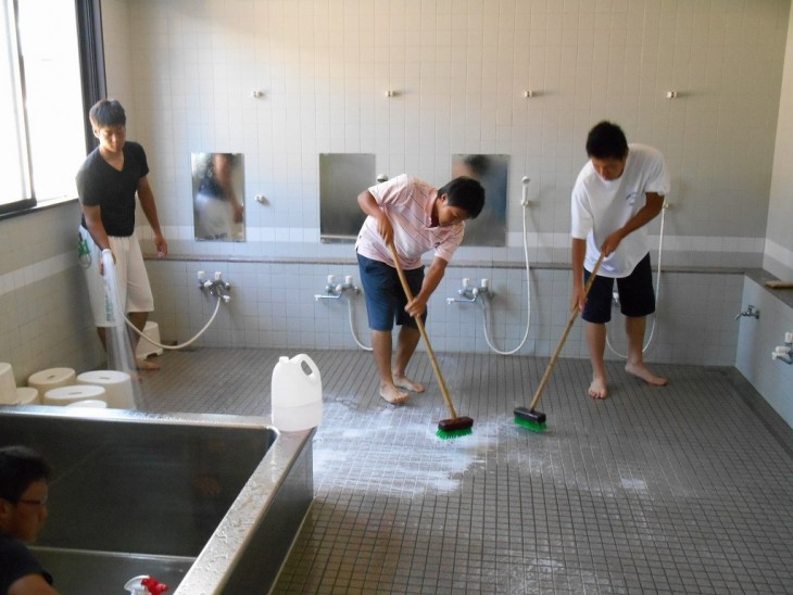 chicos en Japón limpiando los baños de su escuela