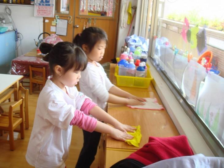 duas meninas japonesas limpando os móveis em suas salas de aula