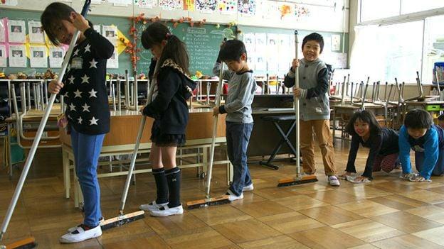 niños japoneses limpiando su aula en la escuela