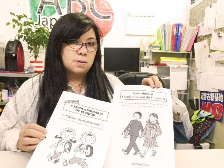 Mulher japonesa mostrando algumas folhas da escola Tsurumi