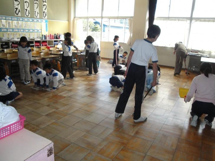 Crianças japonesas fazendo limpeza na sala de aula