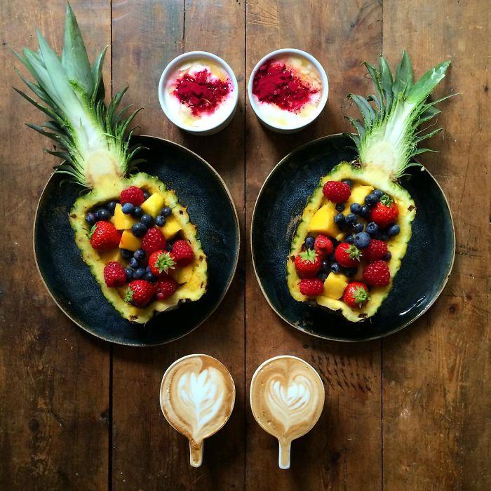 Desayuno simétrico de una piña rellena de fruta con dos tazas de café