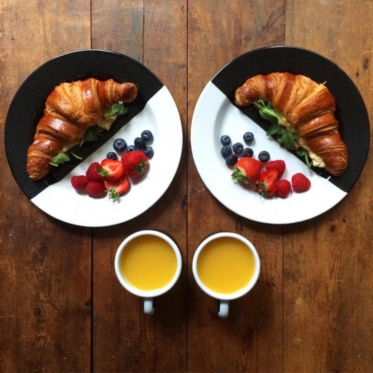 Platillo con cuernitos y frutas rojas simétricas a dos tazas con jugo