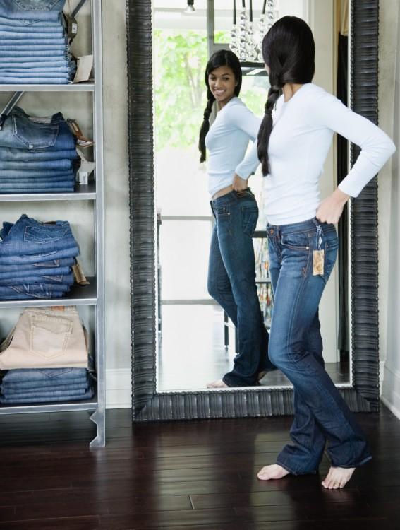 Chica frente a un espejo poniendose un pantalón de mezclilla