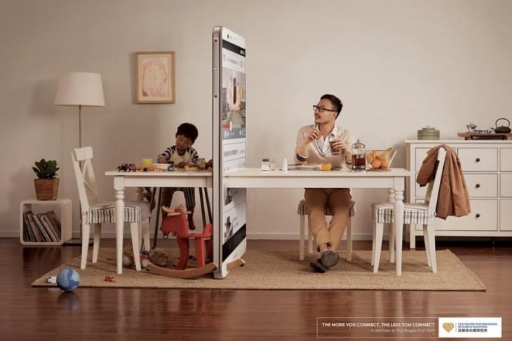 Hombre sentado a la mesa junto a su hijo separados por un celular