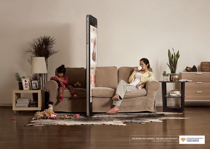 Mujer y una niña sentadas en un sillón separadas por un enorme celular