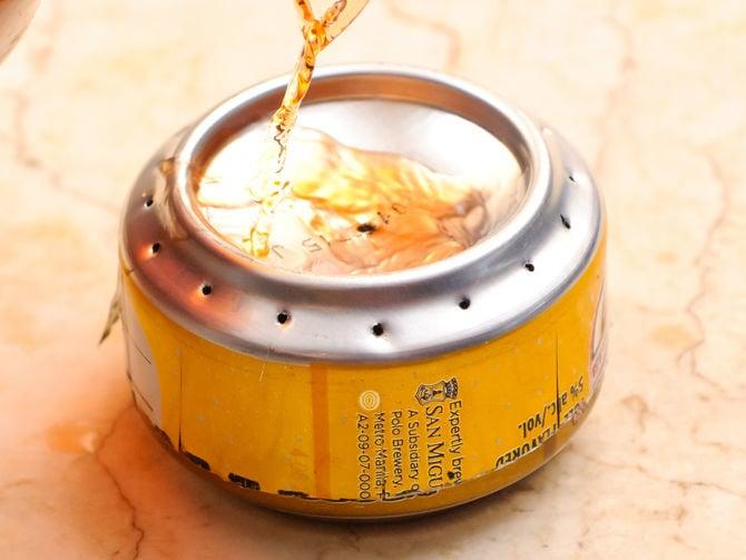 Verter alcohol sobre una lata para hacer un quemado de estufa