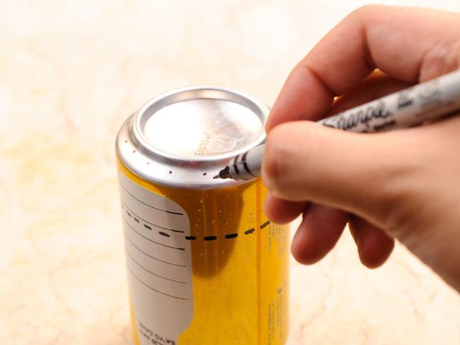mano con un marcador marcando la linea punteada sobre una lata