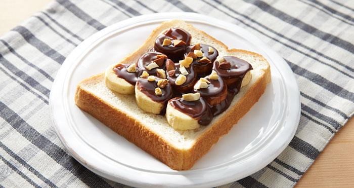 rebanada de pan con oplatano cubierto de chocolate y trozos de cacahuete