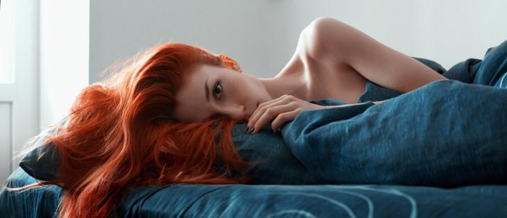 Mujer pelirroja acostada sobre una cama con sabanas azules