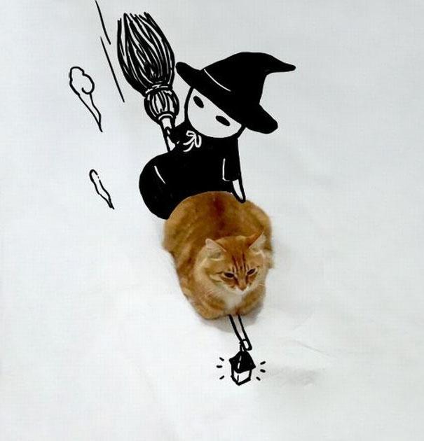 Gato con un dibujo de una bruja sentada sobre él