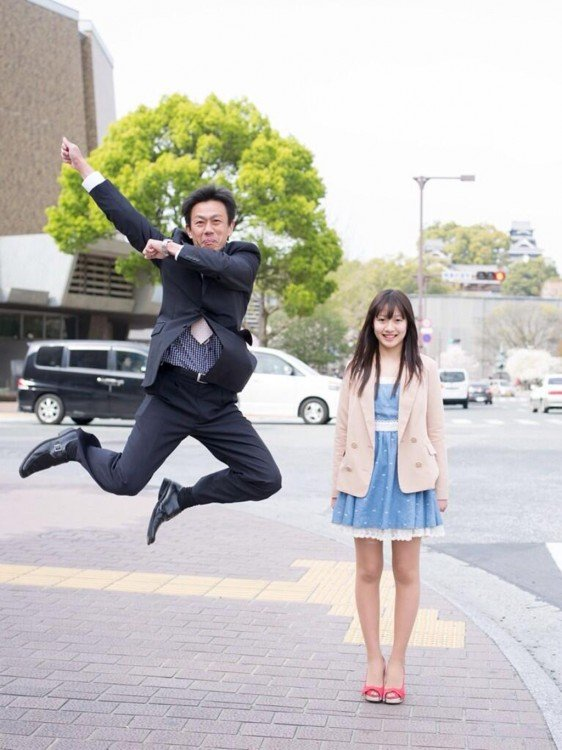 papa saltando con su hija vestida con un traje de mezclilla y un sueter café