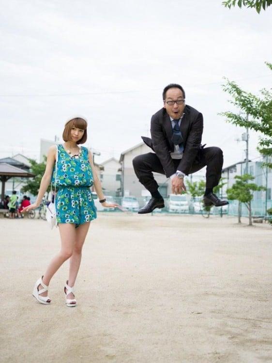 papa brincando como sapo junto a su hija en su traje de ejecutivo ella con un vestido verde y corto