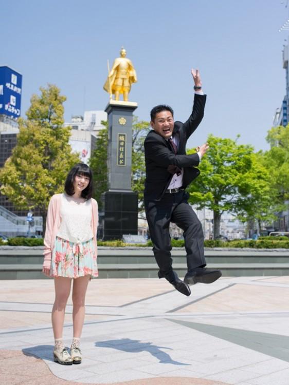papa brincando feliz con una estatua al fondo