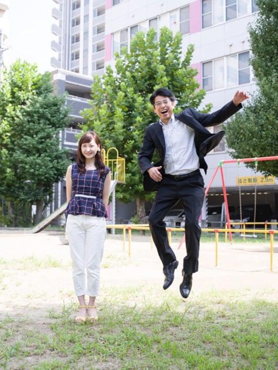 papa brincando junto a su hija con un parque de diversiones como fondo