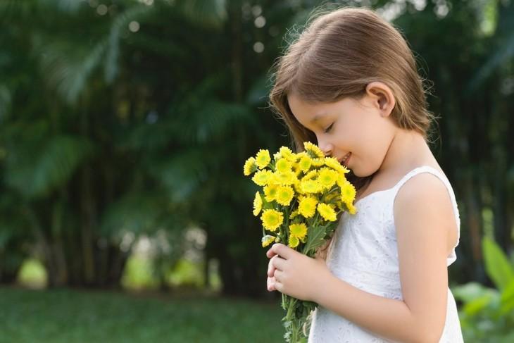 Niña oliendo un ramo de flores