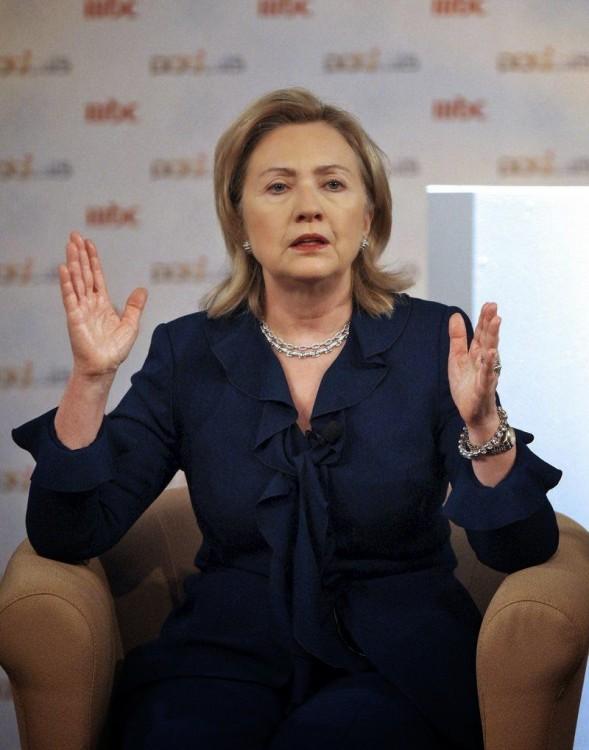 mujer sentada en un sillón hablando con las manos abiertas
