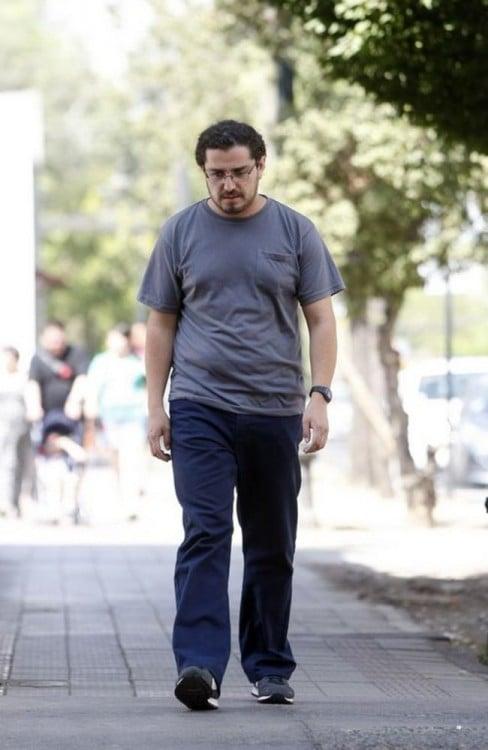 Hombre caminando por la calle con los hombros caídos