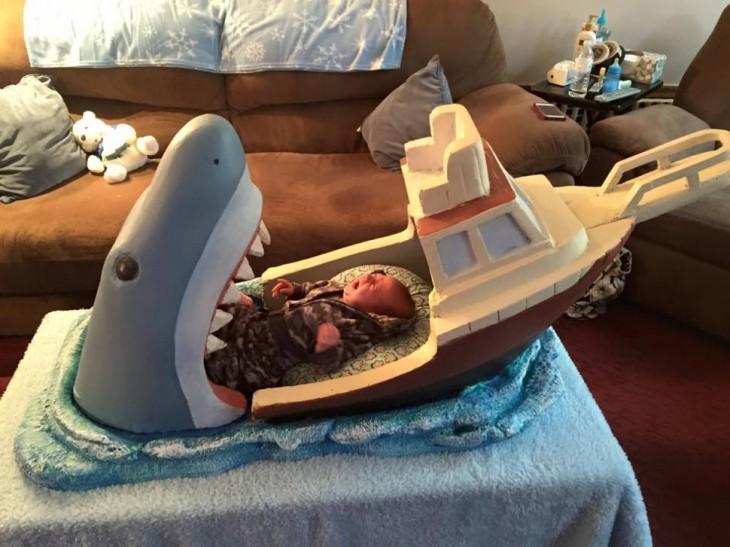 bebé acostado sobre un portabebé en forma de un tiburón a punto de comerse un barco